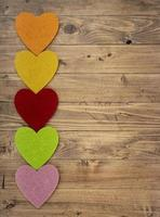 Colored hearts in a row down on a walnut wood background. Concept of St. Valentine's Day