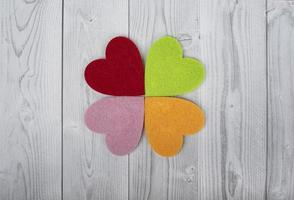 Four coloured hearts on a grey and white wooden background. Concept of St. Valentine's Day