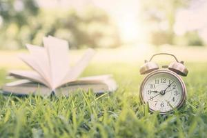 Alarm clock and book in the park photo