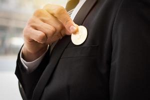 Person putting a coin into the suit pocket