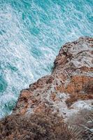 Rock cliff near blue water photo
