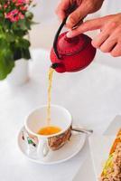 Persona vertiendo líquido rojo sobre una taza de cerámica blanca foto
