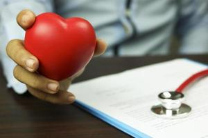 Doctor holding and showing red heart symbol