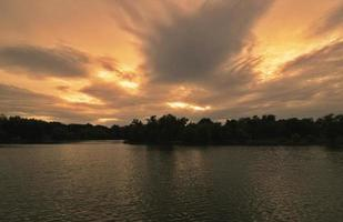 Dark sunset landscape over lake and trees