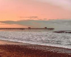 Sea waves crashing on shore during sunset photo