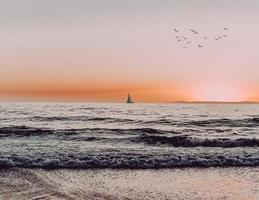 Silhouette of sailboat on sea during sunset photo