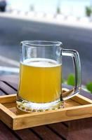 Glass of beer in wooden tray on table