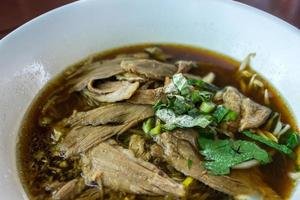 Duck noodle soup in white bowl