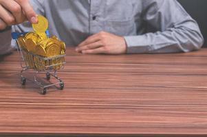 mano con un carrito de compras en miniatura