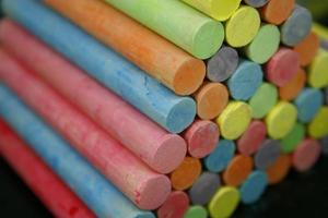 Set of colorful pieces of chalk on blackboard