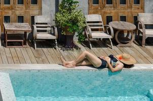 mujer descansando junto a la piscina