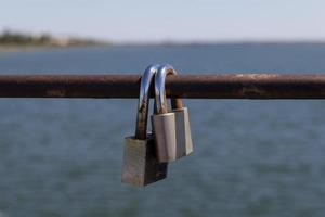 Two padlocks on a metal bar with water and the horizon in the background