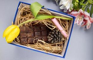 top view of yellow color tulip flower with dark chocolate bar and cone on a straw in a blue present box and a bouquet of alstroemeria colors on white background