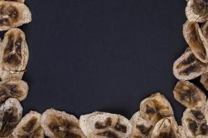 Vista superior de chips de plátano secos sobre fondo negro con espacio de copia foto