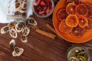 Vista superior de rodajas de naranja secas en un plato y chips de plátano secos esparcidos desde un frasco de vidrio con ramas de canela sobre fondo de madera