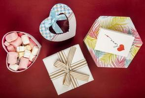 Top view of gift boxes of different shapes and colors and marshmallow in a heart shaped box on red background photo