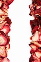 Dried strawberry slices arranged on white background with copy space photo