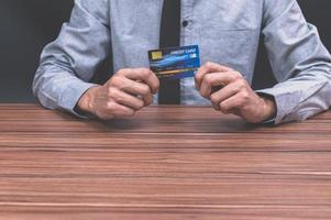 hombre sosteniendo una tarjeta de credito