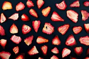 Top view of dried strawberry slices isolated on black background photo