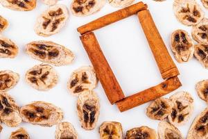 Top view of dried banana chips with cinnamon sticks on white background