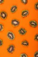 Vista superior de rodajas de kiwi seco aislado sobre fondo naranja foto