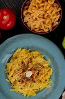 top view of macaroni pasta in plate with tomato and different macaroni types in bowl on wooden background