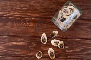Vista superior de chips de plátano secos esparcidos desde un frasco de vidrio sobre fondo de madera con espacio de copia