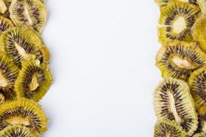 Top view of dried kiwi slices on white background with copy space photo