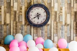 Reloj vintage colgado en el fondo de la pared de madera con globos de colores