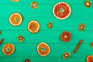 Vista superior de rodajas secas de naranja y pomelo con kiwi seco y ramitas de canela sobre fondo de madera verde