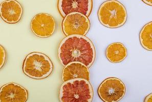 Top view of dried slices of orange and grapefruit arranged on white background