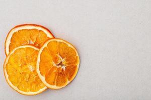 Vista superior de rodajas de naranja secas dispuestas sobre un fondo blanco. foto