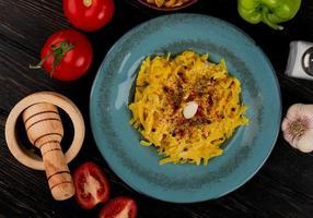 Vista superior de la pasta de macarrones en un plato con tomates enteros y cortados pimienta sal ajo triturador de ajo sobre fondo de madera foto