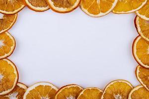Vista superior de rodajas secas de naranja dispuestas sobre fondo blanco con espacio de copia foto