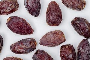 Top view of dried date fruits on white background