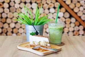 Cerca de la bebida de té verde y pastel banoffee con cobertura de caramelo en una placa blanca sobre fondo de mesa de madera