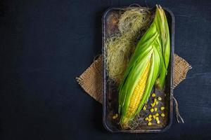 Fresh corn in a tray on a black background