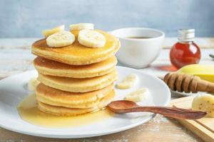 Pancakes topped with honey and bananas