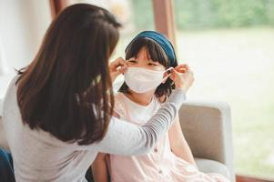 Mother placing mask on daughter
