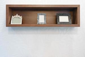 Marco de fotos vacío en estante de madera con fondo de pared blanca