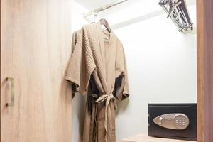 Bathrobe and safe box with electronic lock hidden in the wardrobe at the hotel.