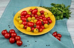 side view of yellow and red tomatoes in plate and green mint leaves on blue cloth background photo