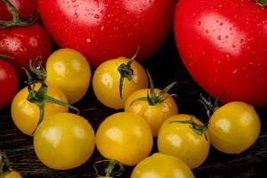 Vista lateral de tomates amarillos y rojos sobre fondo de madera foto