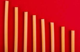 Vista superior de la pasta bucatini sobre fondo rojo. foto