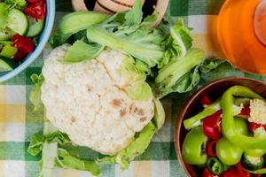 top view of cauliflower with sliced peppers and vegetable salad with melted butter on plaid cloth background