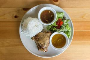 Stewed chicken with rice and salad on white plate