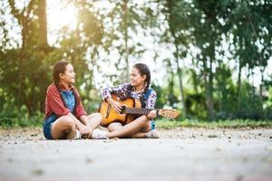 Two girls relaxing and playing guitar