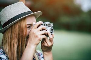 Young woman poses with retro film camera