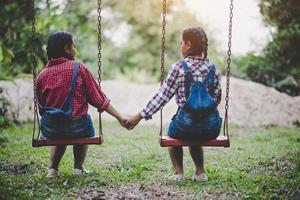 dos niñas sentadas juntas en un columpio foto