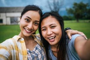 Two teens looking at camera making a selfie photo